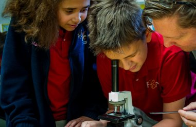 Teacher and Students looking through a microscope